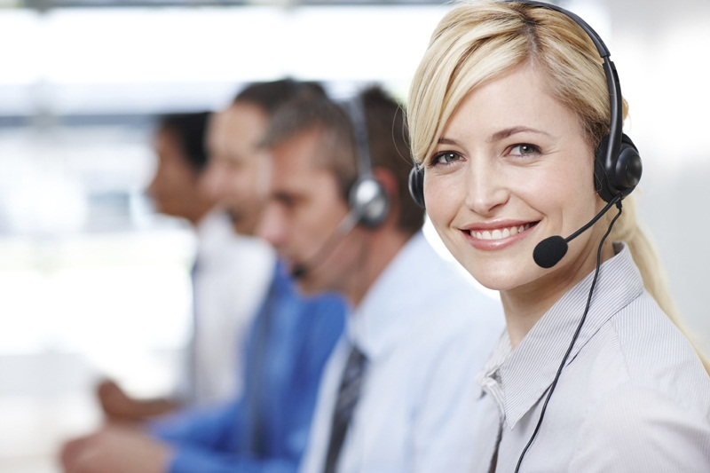 Pretty customer services operator smiling at you with colleagues in background - copyspace