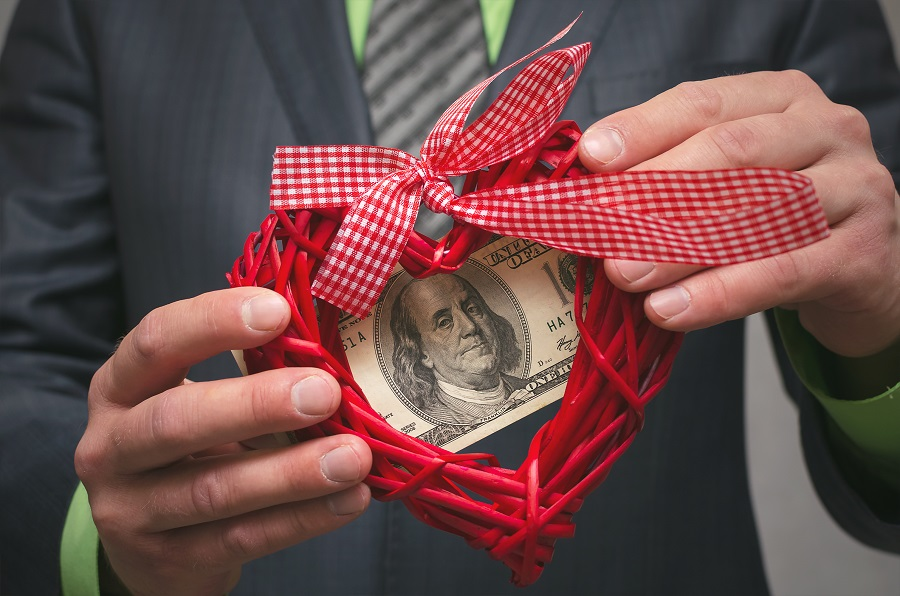 Red heart shape and one hundred dollars in businessman hands. Love for money. Greedy man. .